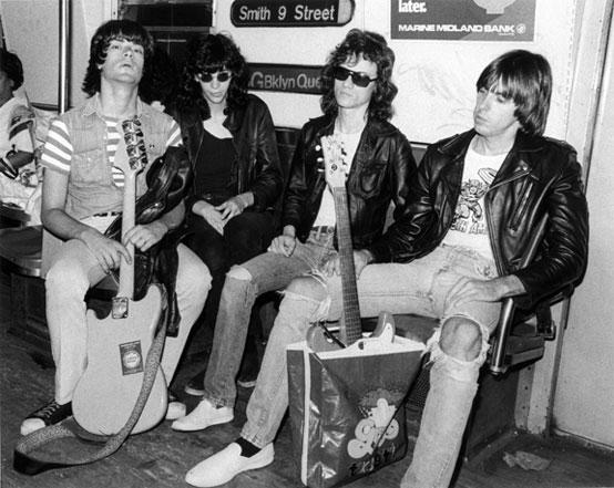 Ramones indo para seu ensaio, levando os instrumentos em sacolas de supermercado por não ter grana para comprar cases de guitarra. Por Bob Gruen.